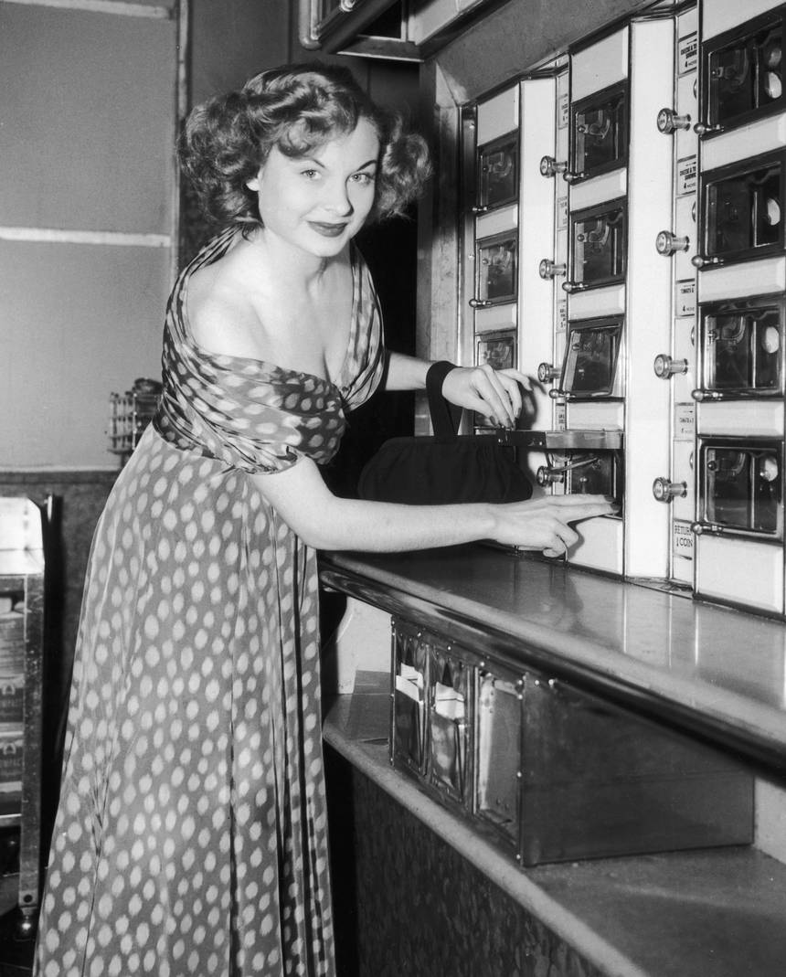 Model Cindy Heller, wearing a low-cut spotted print dress, purchases a snack from a vending machine in an automat.